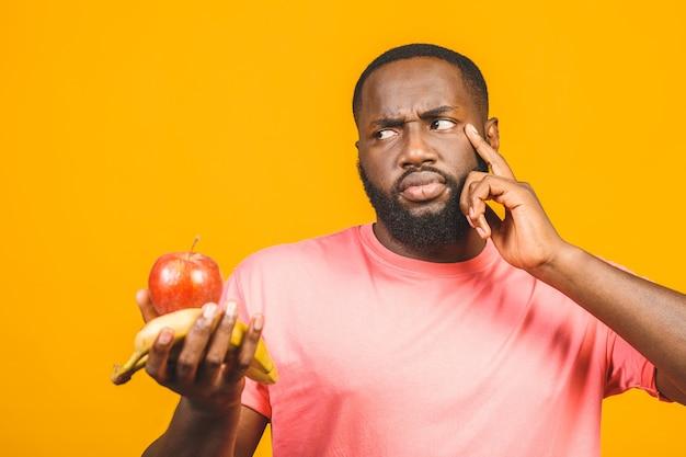 Concetto di dieta. frutti sani della tenuta dell'uomo di colore dell'afroamericano.