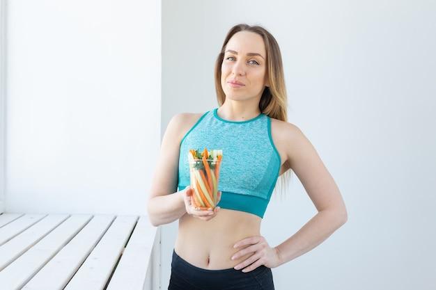 Concetto di dieta - donna di stile di vita sano che tiene le verdure all'interno. giovane femmina che mangia alimento sano.