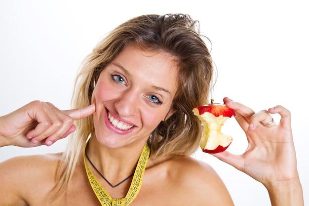 Concetto di dieta: cibo sano, giovane bella donna con una mela mangiata
