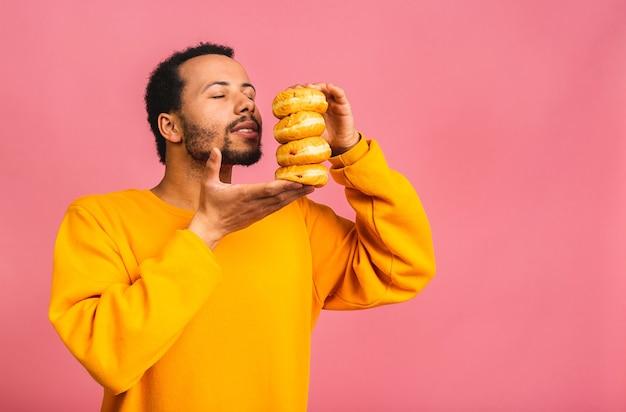 Concetto di dieta. uomo barbuto affamato che mangia ciambelle isolate sul colore rosa.