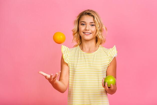 Concetto di dieta. ritratto della piccola ragazza sveglia del bambino dell'adolescente che tiene una mela e un'arancia