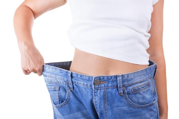Concetto di dieta. donne magre in jeans grandi che mostrano un primo piano estremo di perdita di peso di successo