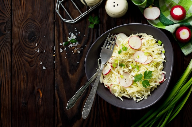 Concetto dietetico di cibo vegetariano insalata estiva con cavolo fresco e ravanello sul tavolo