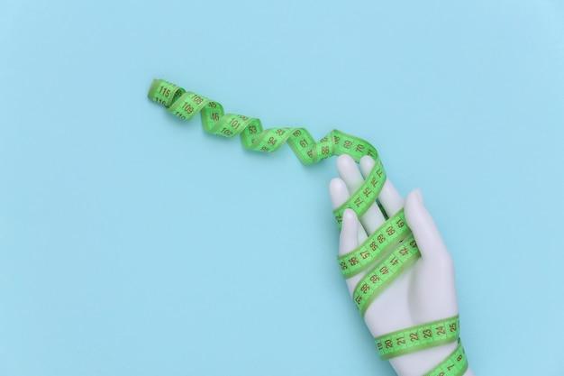Concetto di dieta. manichino bianco avvolto a mano con metro a nastro su sfondo blu