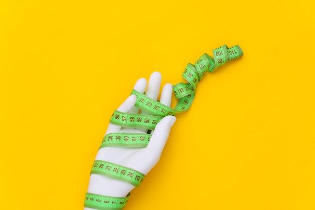 Concetto di dieta. manichino bianco avvolto a mano con metro a nastro su sfondo giallo