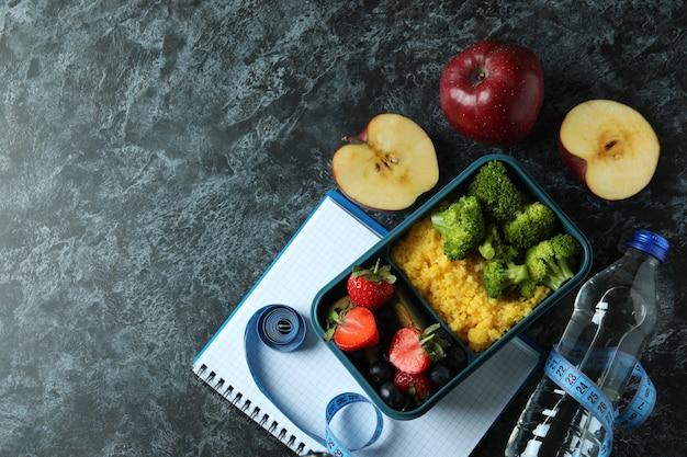Concetto di dieta con scatola del pranzo sul tavolo nero affumicato
