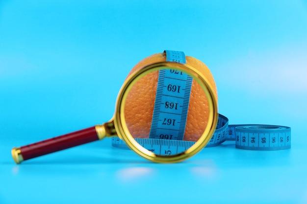Concetto di dieta con metro a nastro, arancia e lente d'ingrandimento per la perdita di peso