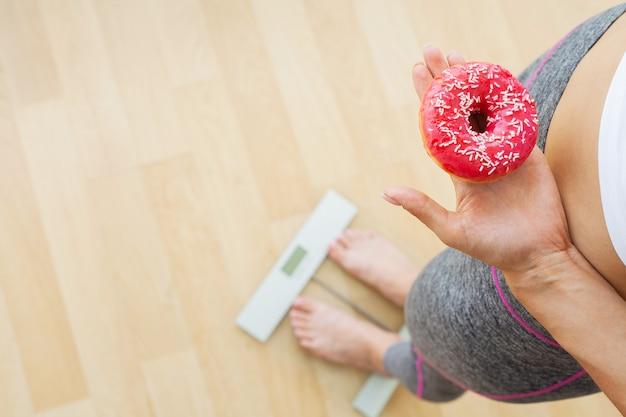 Concetto di dieta, la donna misura il peso su bilance elettroniche mentre si tiene la ciambella calorica