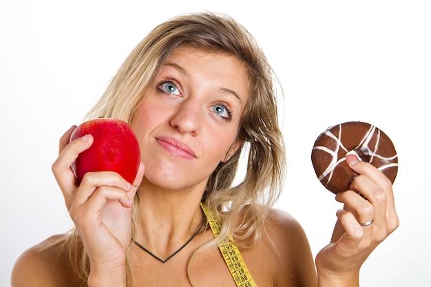 Concetto di dieta: donna nei guai tra mela o ciambelle