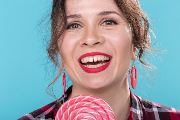 Dieta, dessert e cibo spazzatura - stile pin-up donna close-up con lecca-lecca su sfondo blu