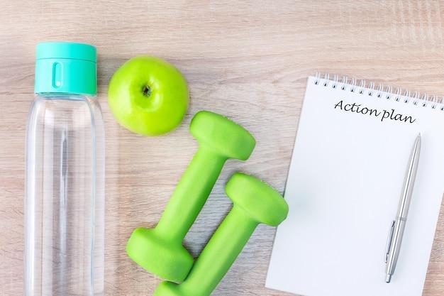 Cibo dietetico, concetto di fitness con manubri, frutta, bottiglia di acqua potabile e notebook sulla scrivania in legno.