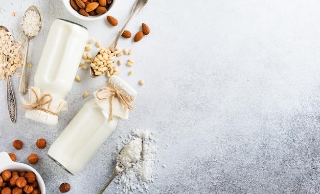 Concetto sano di dieta. latte e mandorle vegetali fatti in casa dieta, ricci, nocciole, farina d'avena, riso e cocco su un tavolo grigio. vista dall'alto.