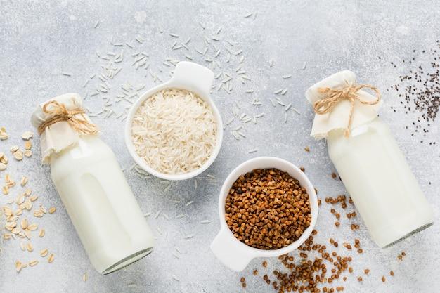 Concetto sano di dieta. latte dietetico vegetariano da riso ai cereali, grano saraceno e avena, tre tipi di fatti in casa sul tavolo delle tendenze in cemento grigio. copia spazio. vista dall'alto.
