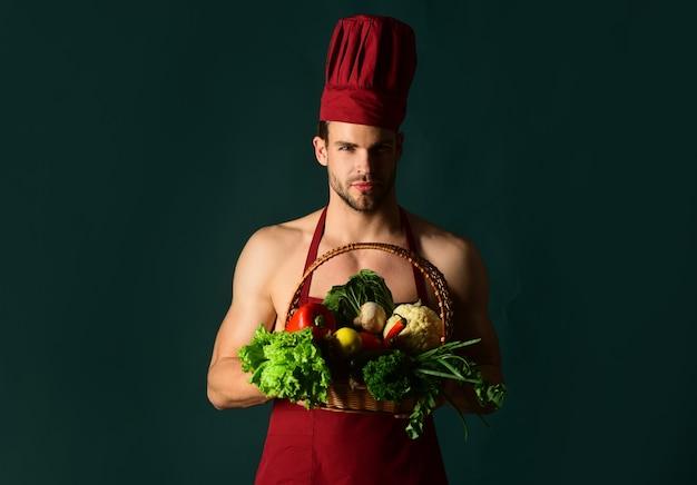 Dieta cibo sano cucina concetto vegetariano attraente chef maschio vestito con abiti da cuochi detiene