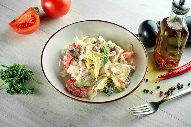 Dieta e sana insalata con carne di manzo, verdure e pomodori, parmigiano, servita in un piatto bianco su un tavolo di legno. cibo del ristorante