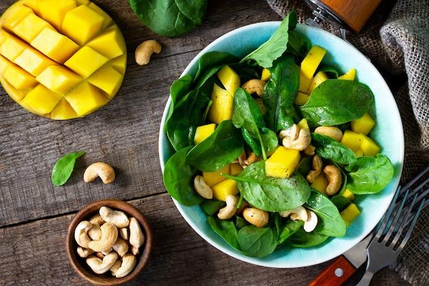 Menù dietetico insalata salutare con spinaci, mango, noci pecan e salsa vinaigrette vista dall'alto