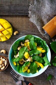 Menu dietetico cibo vegano insalata salutare con spinaci, mango, noci pecan e salsa vinaigrette vista dall'alto