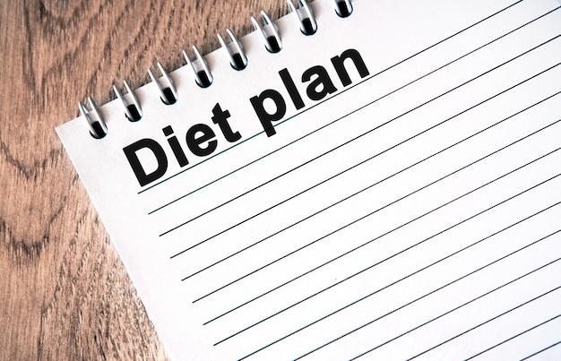 Piano di dieta - testo nero su un taccuino bianco con linee su un tavolo di legno