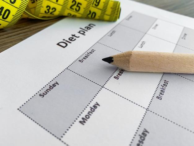 Concetto di piano di dieta. nastro di misurazione e programma dietetico su fondo di legno.