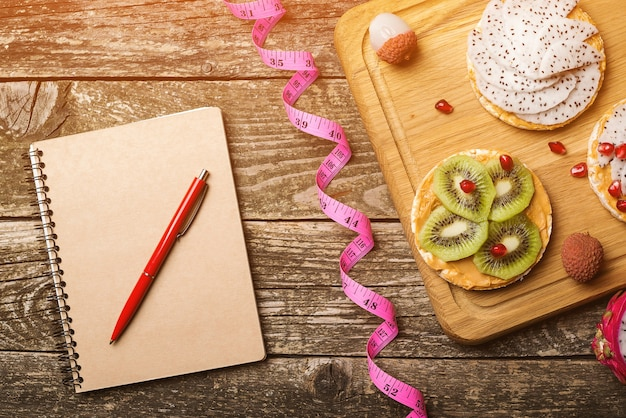 Concetto di piano di dieta. notebook per menu o programma, metro a nastro e spuntini sani.