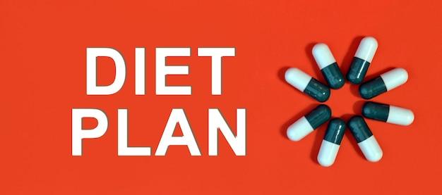 Piano di dieta - testo bianco su sfondo rosso con capsule di pillola