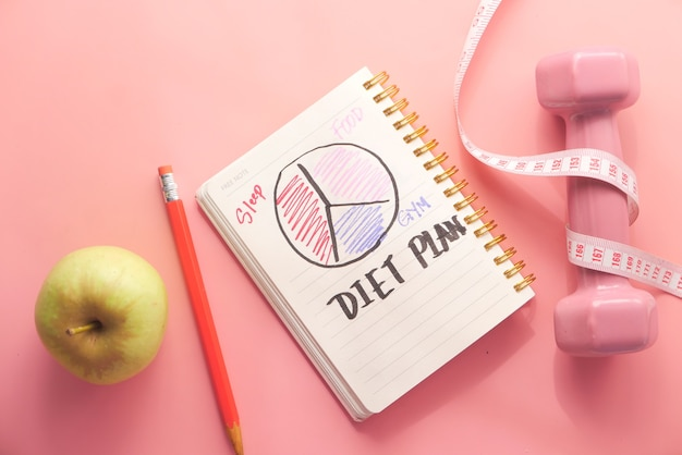 Piano dietetico con mandorle, manubri, mela sul tavolo.