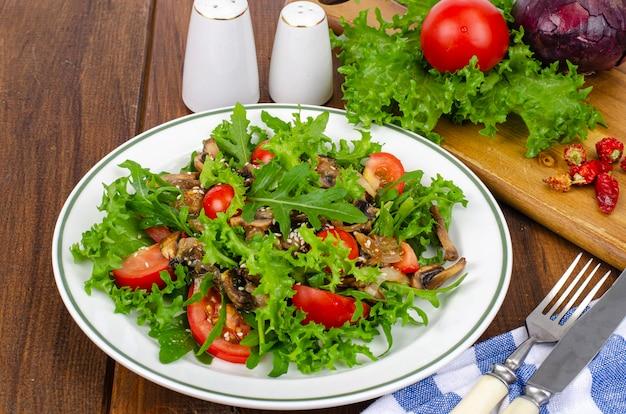 Insalata dietetica di foglie di rucola, pomodori e funghi fritti su un tavolo di legno. foto dello studio.