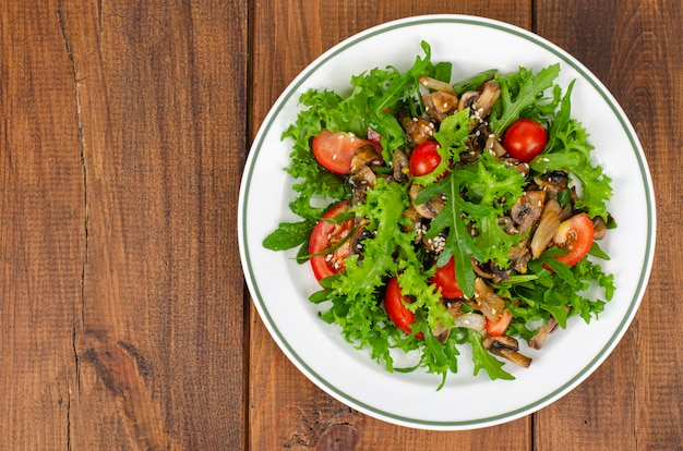 Insalata dietetica di foglie di rucola, pomodori e funghi fritti su un tavolo di legno.