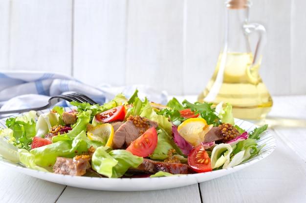 Insalata dietetica con petto d'anatra magre, erbe fresche, verdure e salsa alla senape su legno chiaro