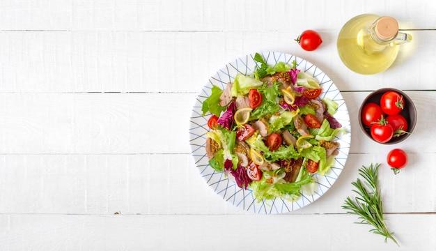 Insalata dietetica con petto d'anatra magre, erbe fresche, verdure e salsa alla senape