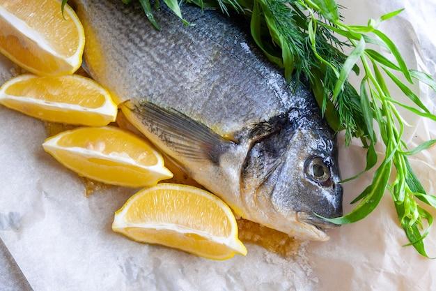 Pesce di dorado di mare di dieta preparato per la cottura con il primo piano del limone e delle erbe fresche