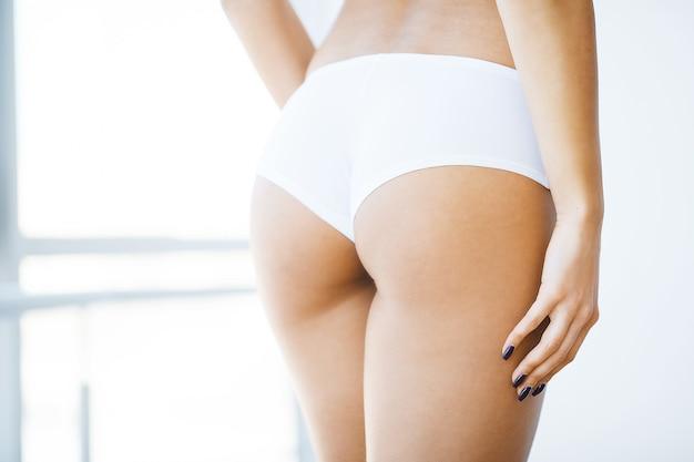 Dieta e cura della pelle. bella figura snella della donna con un'arancia vicino al suo asino