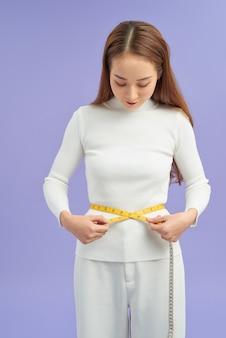 Concetto di dieta, sport e brughiera - bella donna sportiva con nastro adesivo di misurazione