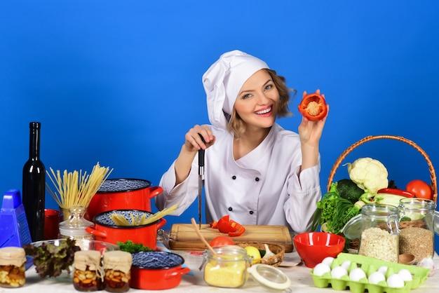 Dieta vegetariana sano cibo biologico cucina sorridente chef donna tiene in mano pepe e coltello
