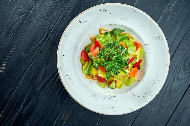Insalata dietetica e vegetariana di verdure miste e lattuga con salsa di arachidi, servita in un piatto bianco su un tavolo di legno nero