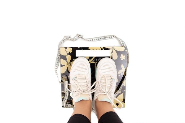 Dieta e peso, i piedi nelle scarpe da ginnastica sono sulla bilancia. sfondo bianco. copia spazio. vista dall'alto.