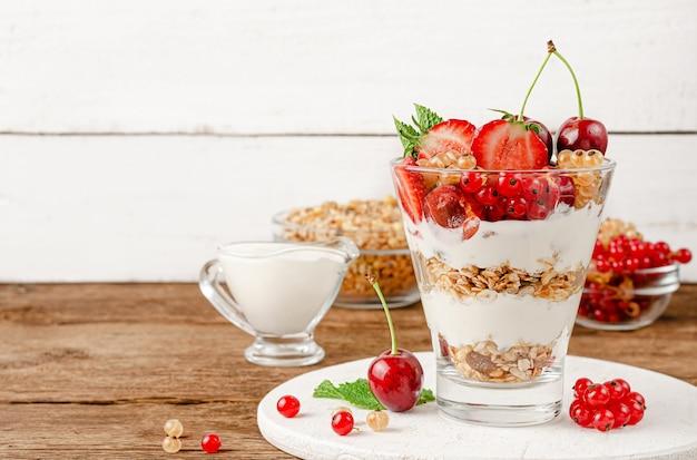 Colazione dietetica di muesli con frutti di bosco e yogurt su fondo di legno bianco. copia spazio
