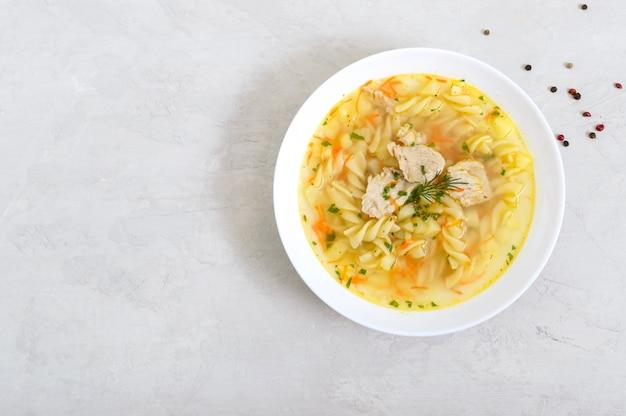 Zuppa di pollo dietetica con fusilli in una ciotola bianca su sfondo chiaro. la vista dall'alto copia spazio.