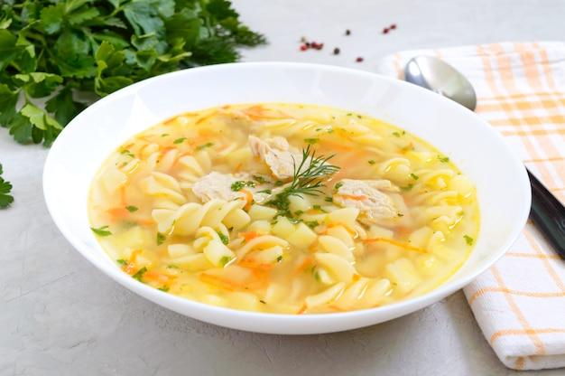 Zuppa di pollo dietetica con fusilli in una ciotola bianca su sfondo chiaro