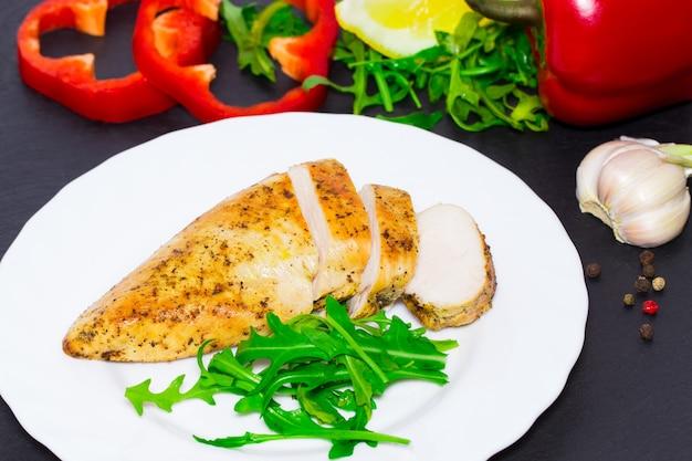 Cucina dietetica - petto di pollo alla griglia con foglie di rucola e verdure su sfondo scuro.