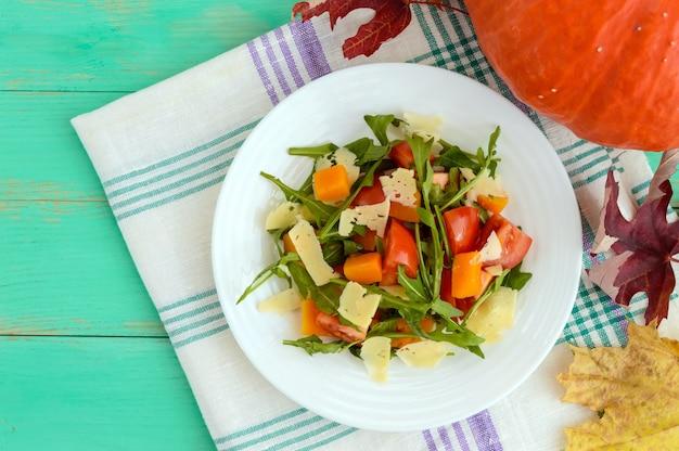 Insalata dietetica con zucca, pomodori freschi, rucola e parmigiano. la vista dall'alto