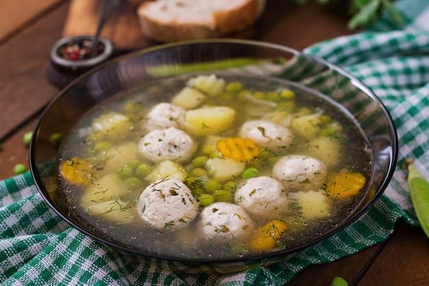 Zuppa dietetica con polpette di pollo e piselli in una ciotola di vetro su un tavolo di legno.