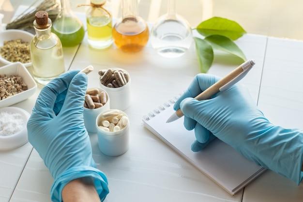 Capsule e ingredienti dell'integratore alimentare. la mano di un farmacista scrive in un taccuino