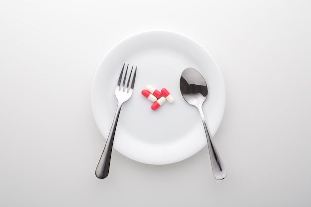 Integratore alimentare sul piatto bianco con forchetta e cucchiaio, vista dall'alto