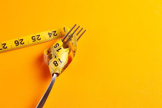 Concetto di dieta con forchetta e metro