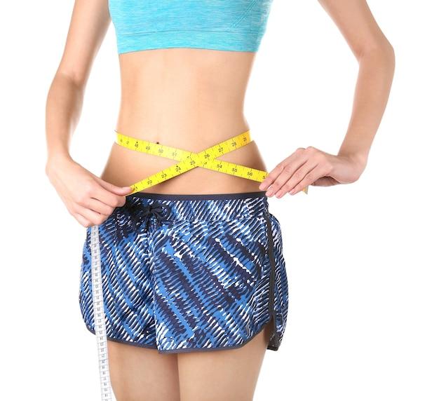 Concetto di dieta. donna con nastro adesivo di misurazione isolato su bianco