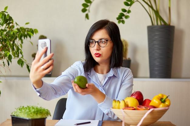 Donna dietista che registra su uno smart phone il suo vlog sul mangiare sano