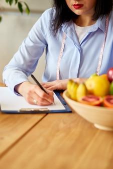 Donna dietista che scrive un programma di dieta, con frutta e verdura sane