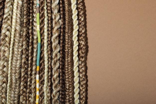 Diverse trecce afro, trecce realizzate con materiali kanekalon su sfondo marrone, copia dello spazio