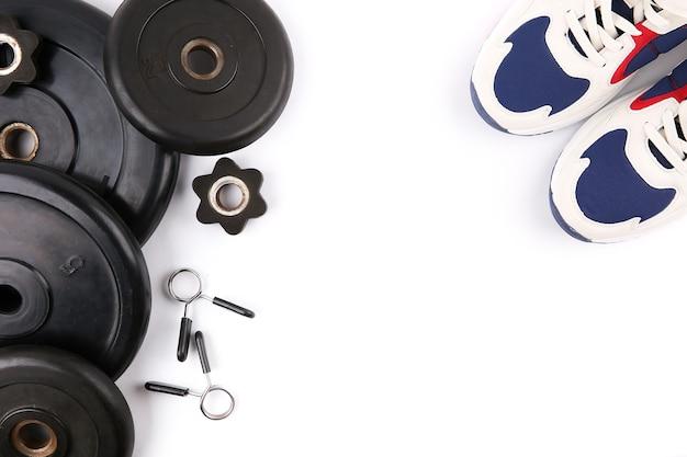 Diversi dischi bilanciere e scarpe da ginnastica su uno sfondo bianco con spazio di copia